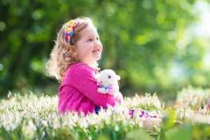 Little girl playing with bunny on Easter egg hunt